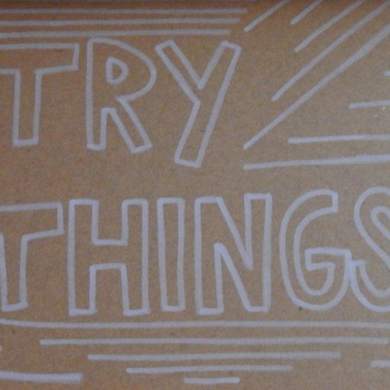 Texte écrit à la main : « Try things ».