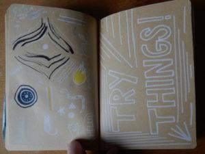 Cahier. Sur la page de gauche, on peut voir des doodles (petits dessins). Sur la page gauche, on peut lire « Try things » avec des lignes.