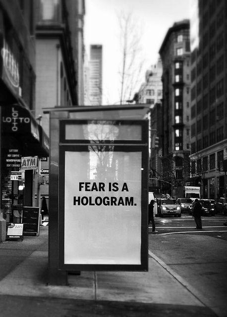 Panneau publicitaire. On peut y lire « Fear is a hologram » (« La peur est un hologram »).