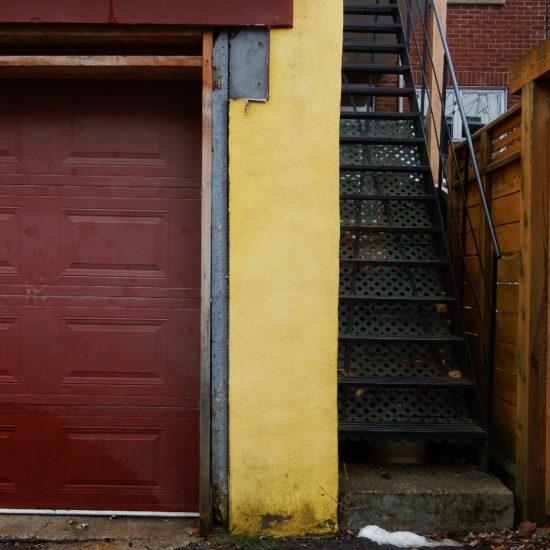 Garage jaune moutarde avec une porte rouge foncé.