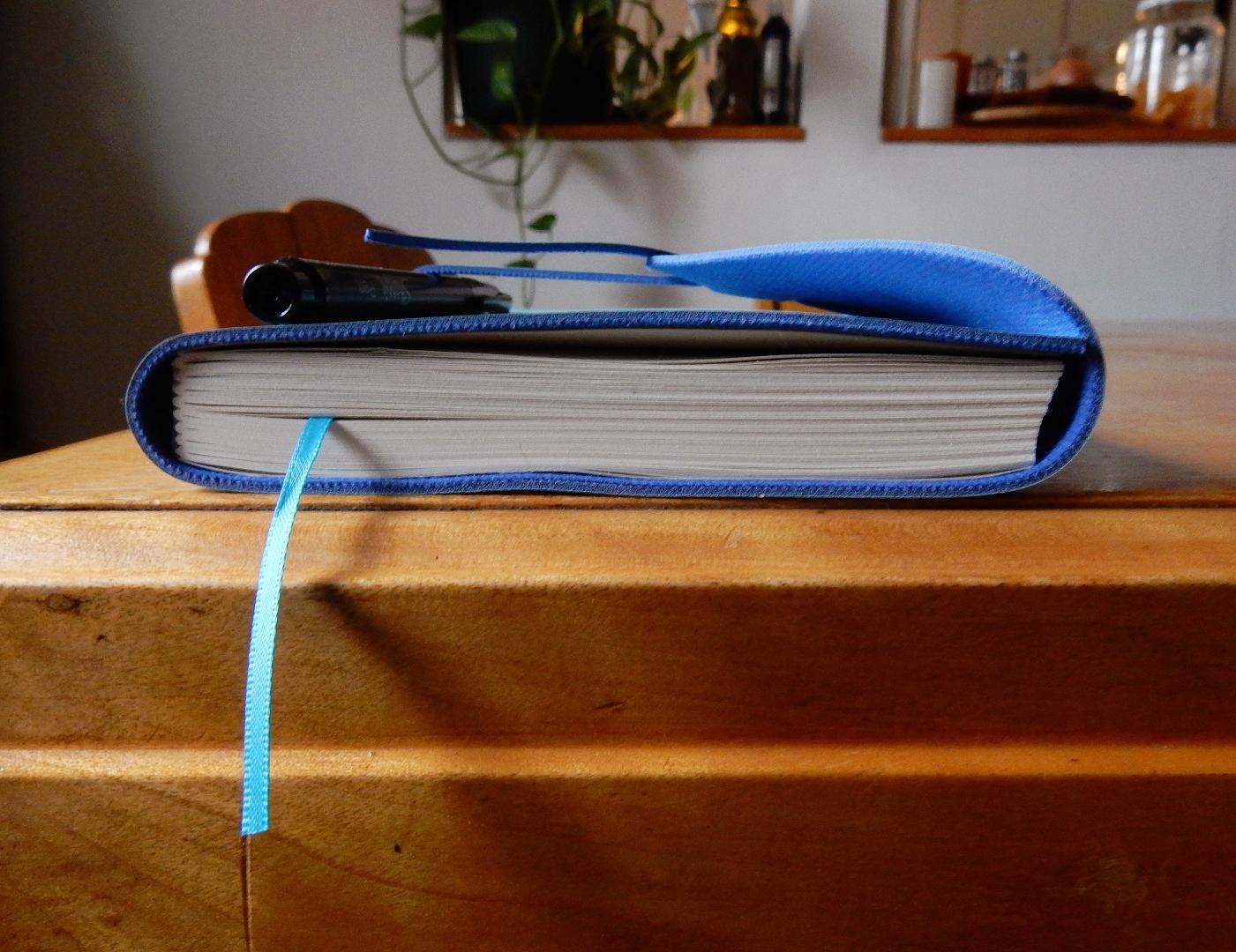 Cahier bleu pâle et stylo noir sur une table en bois.